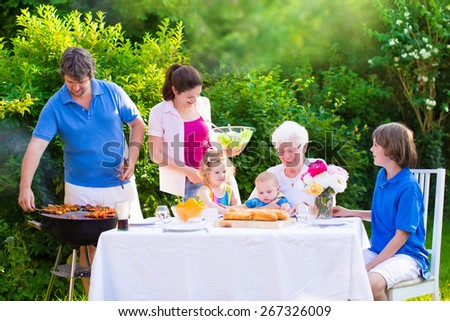Grill barbecue backyard party. Happy big family, mother, father, teen son, cute toddler daughter and baby, enjoying BBQ lunch with grandmother eating grilled meat in the garden with salad and bread.  - stock photo