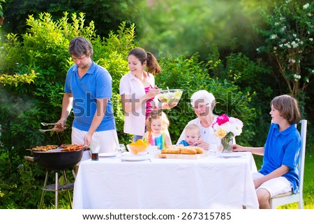 Grill barbecue backyard party. Happy family, mother, father, kids, teen son, toddler daughter and little baby, enjoying BBQ lunch with grandmother eating grilled meat in garden with salad and bread.  - stock photo
