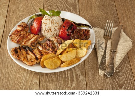 Grill chicken and pilav pilaf and potatoes on wooden background - stock photo