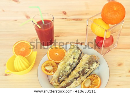 Grill fish ( Merluccius fish) with sour cream, olive oil and orange fruit with garlic and orange juice. Meal serving with tomato fresh on the wood. Mediterranean cuisine. - stock photo