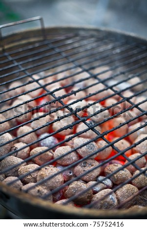 Grill grate with glowing coals in the background - stock photo