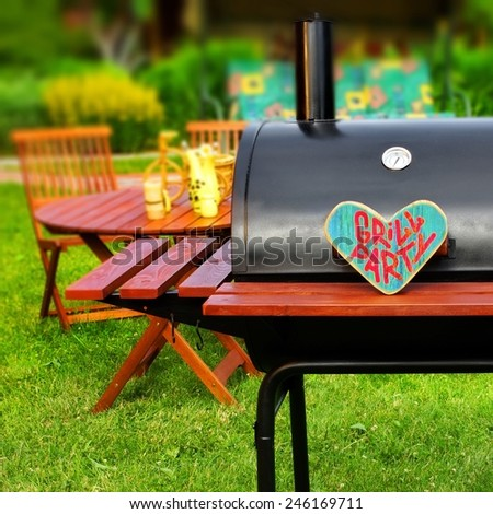 Grill Party Sign on Wood Heart. BBQ Appliance and wooden furniture in the Background. Barbecue Party Scene. - stock photo