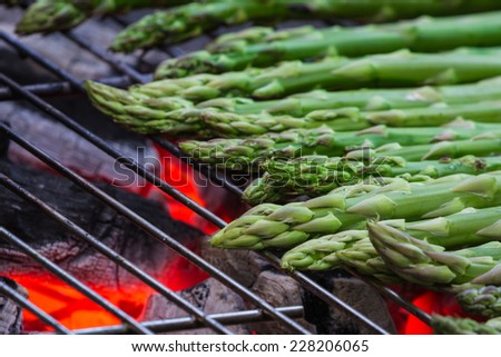 grilled asparagus on an outdoor grill with open flame - stock photo