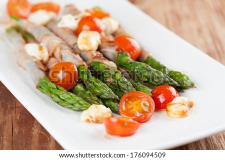 Grilled asparagus with prosciutto, mozzarella and cherry tomatoes - stock photo