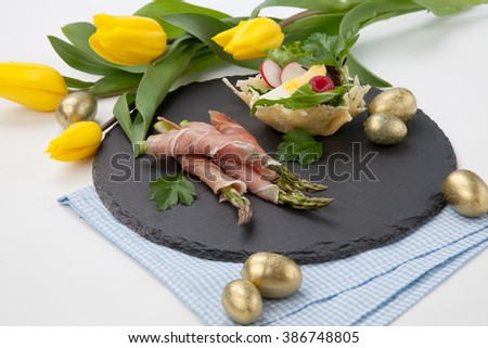 Grilled asparagus wrapped in prosciutto and parmesan baskets filled with fresh garden salad. Easter decorated eggs, tulips flowers, holiday theme. - stock photo