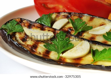 Grilled aubergine served with garlic on white plate - stock photo