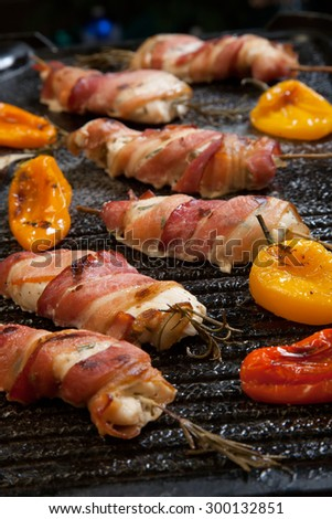 Grilled bacon-wrapped chicken tenders with lemon and rosemary on the grill wih grilled vegetables - peppers, and and eggplant. - stock photo