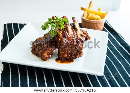 Grilled barbecue spareribs and barbecue sauce with parsley  and french fried on white plate - stock photo