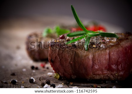 Grilled bbq steak on wooden background - stock photo