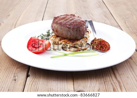 grilled beef fillet medallions on noodles with tomatoes and thyme twigs on white plate over wood - stock photo