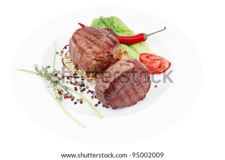grilled beef fillet medallions with thyme and red hot chili pepper on plate isolated over white background - stock photo