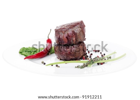 grilled beef fillet pieces on noodles , red hot chili pepper with tomato and green salad leaf on white plate isolated over white background - stock photo