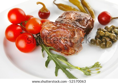 grilled beef meat medallion with  tomatoes on white plate