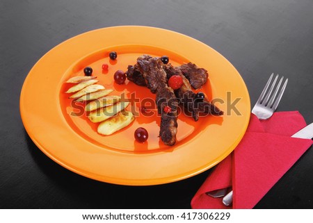 grilled beef meat with berries fried potatoes and cherry under sweet honey sauce on orange plate over black wooden table - stock photo
