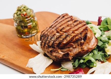 grilled beef on salad on wooden plate - stock photo