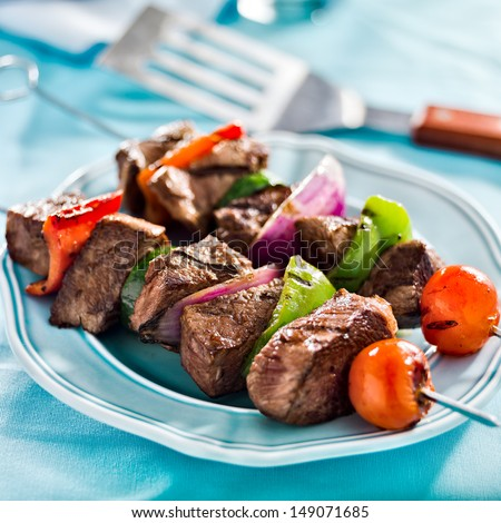 grilled beef shishkabobs on table close up - stock photo