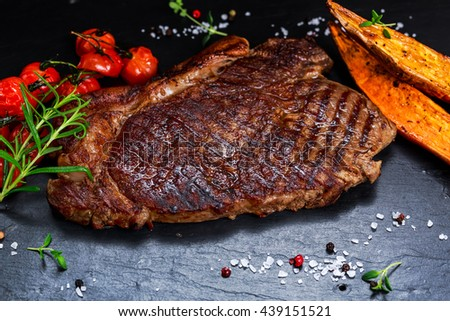 Grilled Beef Sirloin Steak on blue stone background, with vegetables. - stock photo