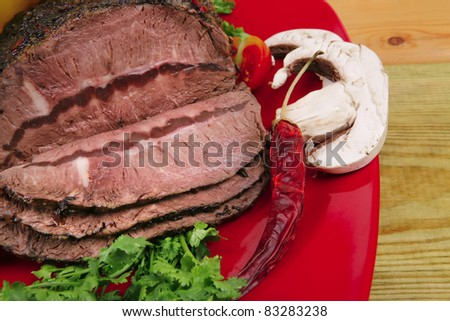 grilled beef sliced on red plate over wood - stock photo