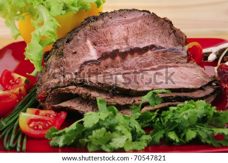 grilled beef sliced on red plate over wood . shallow dof - stock photo