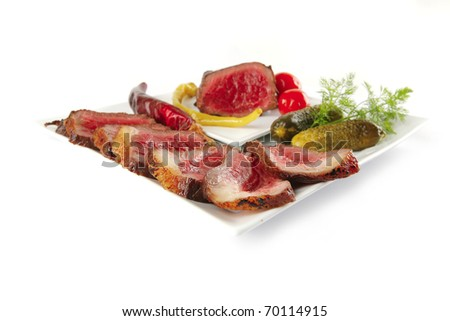 grilled beef slices and vegetables on white plates . isolated over white . shallow dof - stock photo