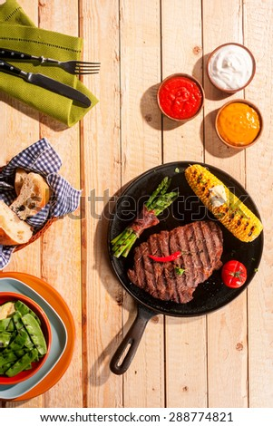 Grilled beef steak, asparagus bacon wraps and corn on the cob served on a wooden outdoor table at a summer BBQ with assorted dips and sauces - stock photo