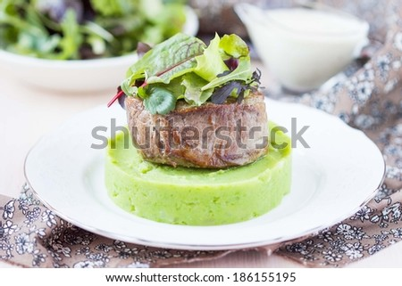 Grilled beef steak, green mashed potatoes with peas, herbs, beautiful presentation in restaurant - stock photo