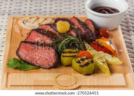 Grilled beef steak on wooden board on a light background restaurant - stock photo