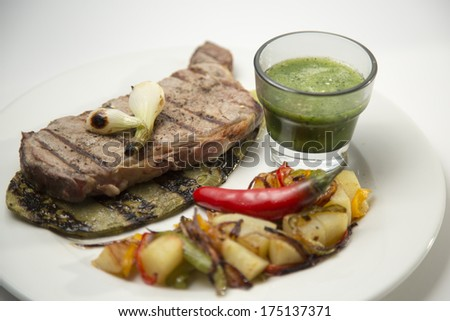 Grilled beef steak served on a cactus, with salsa and vegetables. Isolated on white. - stock photo