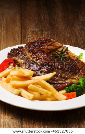 Grilled beef steak served with French fries and vegetables on a white plate.