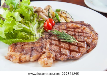 Grilled beef steak served with fresh salad