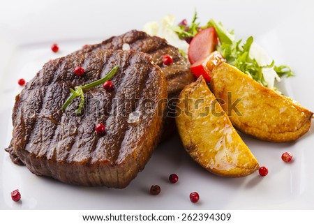 Grilled beef steak with baked potatoes and vegetables on plate