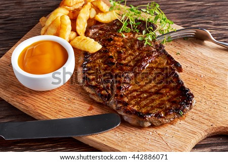 Grilled Beef Steak with Chips and Mango souce on wooden board. - stock photo