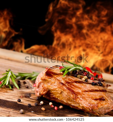 Grilled beef steak with flames on background - stock photo