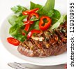 Grilled beef steak with fresh vegetables salad on a plate. - stock photo