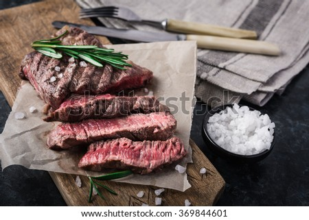 Grilled beef steak with rosemary and salt on cutting board - stock photo