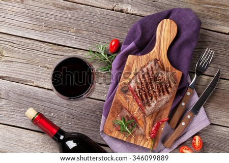 Grilled beef steak with rosemary, salt and pepper and wine bottle on wooden table. Top view with copy space - stock photo