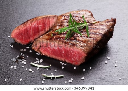 Grilled beef steak with rosemary, salt and pepper on black stone plate - stock photo