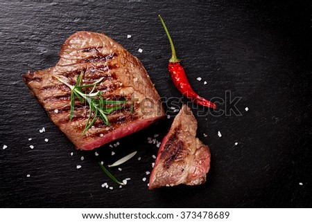 Grilled beef steak with rosemary, salt and pepper on black stone plate. Top view with copy space - stock photo