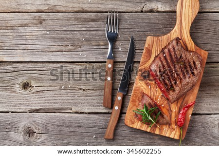 Grilled beef steak with rosemary, salt and pepper on wooden table. Top view with copy space - stock photo