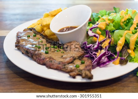 Grilled beef steak with salad and french fries - stock photo