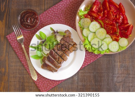 Grilled beef steak with salad and sauce on wooden table at white plate. Salad with tomatoes and cucumbers and sauce barbecue. Leafs of basil as decoration. - stock photo
