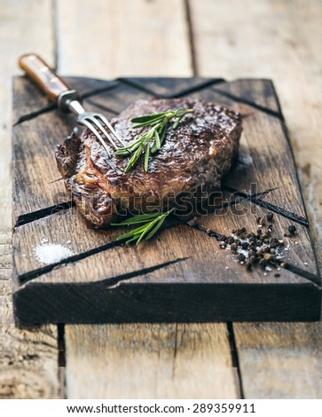 Grilled beef steak with salt, pepper and rosemary on meat cutting board on dark wooden background - stock photo