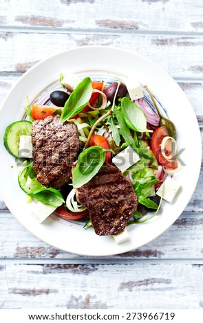 Grilled beef steaks with salad - stock photo