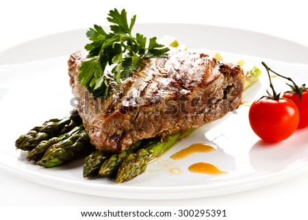 Grilled beefsteak and asparagus on white background - stock photo
