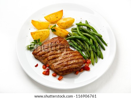 Grilled beefsteak, baked potatoes and vegetables - stock photo