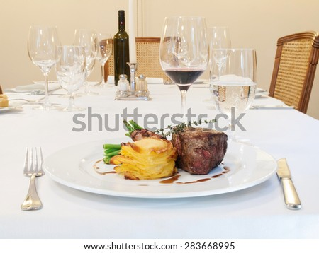 Grilled beefsteak with beans in bacon and gratinated potatoes
