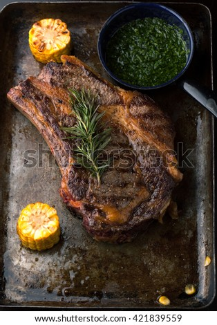 Grilled Black Angus Steak Ribeye  with rosemary and corn on iron pan on wooden background