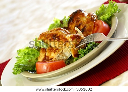 Grilled boneless chicken breast with bbq sauce, salad greens and tomatoes.