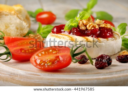 Grilled brie cheese with cranberry jam and walnuts on white wooden background - stock photo