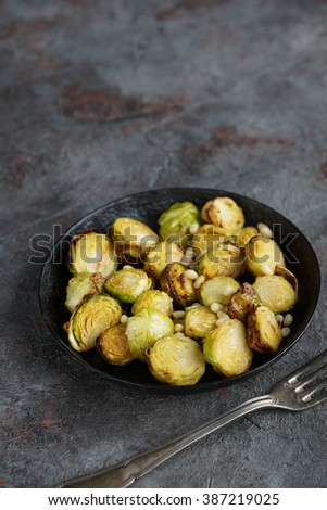 Grilled brussel sprouts on black iron plate on a stone background - stock photo